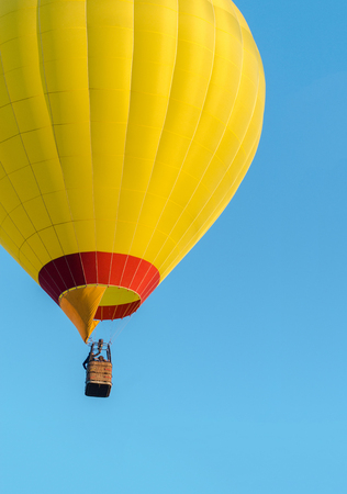 Yellow hot air balloon flying on blue sky background