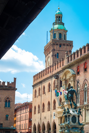 locality: Piazza Maggiore in Bologna old town tower of hall with big clock and blue sky on background. Italy