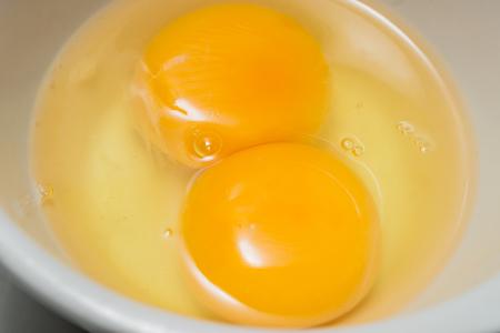 cup four: Fresh Eggs, Twin Egg Yolk in Glasses Bowl. closeup