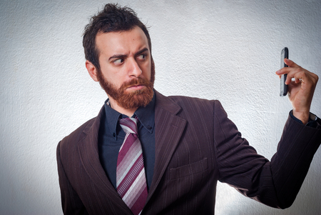 burned out: Young businessman looking angry on his cell phone Stock Photo