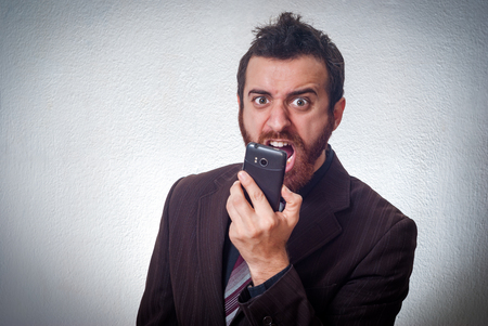 burned out: Angry young businessman shouting on the phone Stock Photo