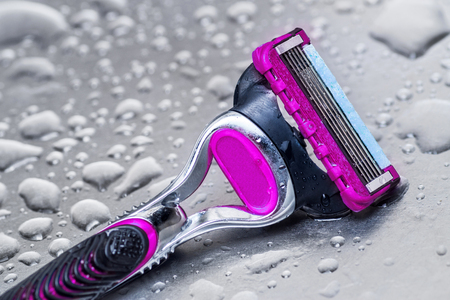 black metallic background: wet disposable razor woman isolated.closeup