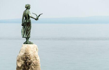 Opatija, Croatia - April 08, 2019: Famous Statue on rocks,  Maiden girl holding a seagull and facing the Adriatic Sea in Opatija, Croatia