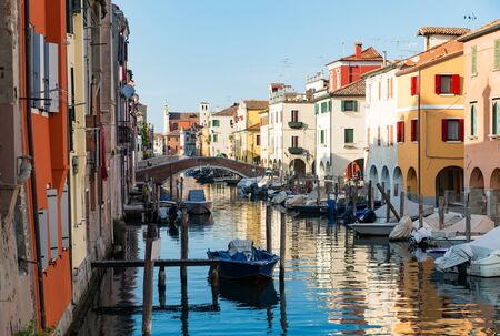 Chioggia, Venice, Italy: city landscape with canal, ancient bridge, boats and colorful reflections on the water in the picturesque old town Archivio Fotografico