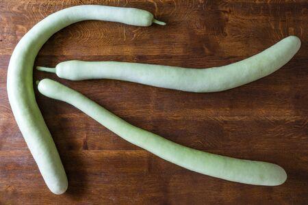 Sicilian vegetable: zucchini lagenaria longissima on the wood table Archivio Fotografico
