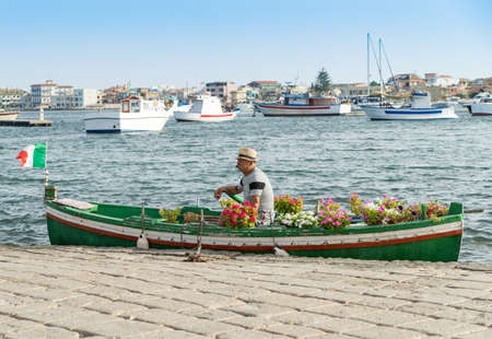 MARZAMEMI, ITALY - JULY 22 2018: fisherman on old boat decorated with flowers in the typical port of Marzamemi, Sicily