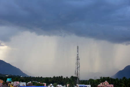 Rain shower falling from dark cumulus clouds