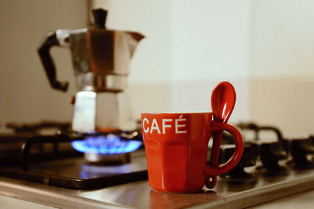 retro styled imagery: red coffee cup and  vintage coffeepot on kitchen stove