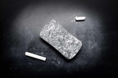 chalk eraser: piece of chalk and eraser on blackboard