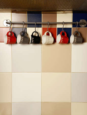 organized group: Colorful coffee cups on hooks