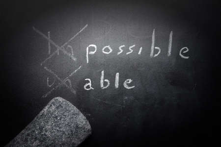 able to learn: positive thinking concept handwritten on black chalkboard with modified impossible unable word