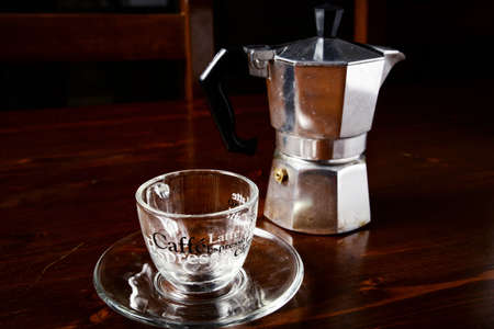 coffeepot: glass  coffee cup and  vintage coffeepot on dark wooden table