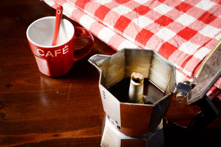 coffeepot: top view of checkered napkin on wooden table with red coffee cup and  vintage coffeepot
