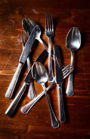 fork spoon: old used cutlery  on dark wooden table Stock Photo