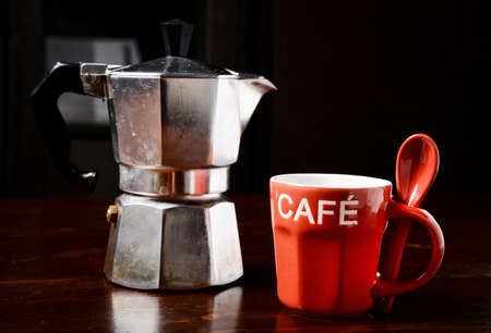coffeepot: red coffee cup and  vintage coffeepot on dark wooden table