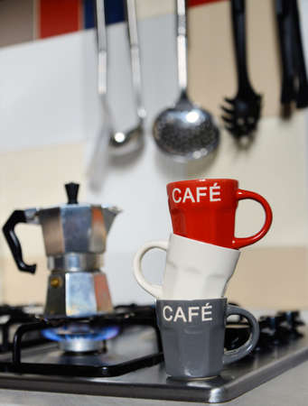 coffeepot: stacked coffee cup and  vintage coffeepot on kitchen stove Stock Photo