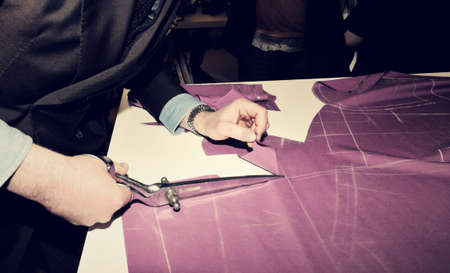 bespoke: Tailor cutting fabric for bespoke suit Stock Photo