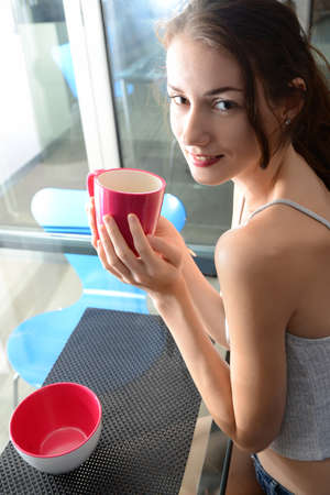 female legs: beautiful young woman with pink cup