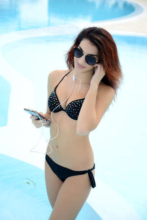 happy beautiful young woman listen music by the pool