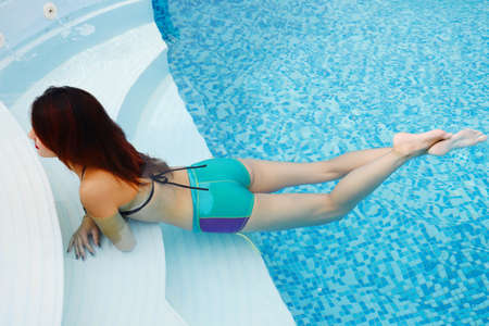 beautiful young woman relaxing in water by the swimming pool