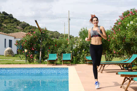 beautiful young woman running by the swimming pool