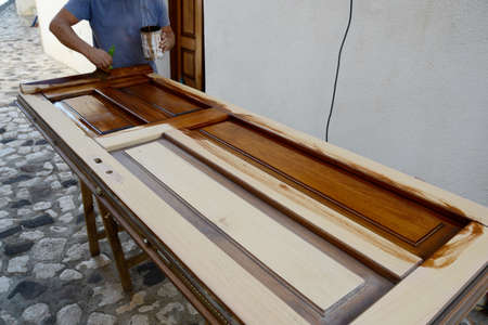 wood door: carpenter painting a wood door