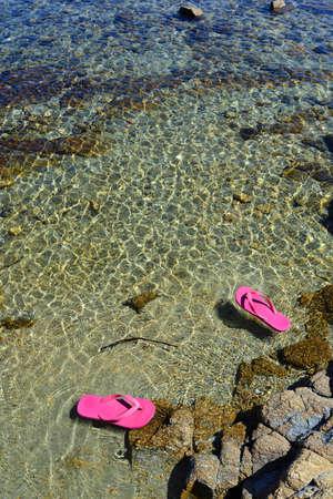 sandalias: Rosa flips flops flotando en el agua de mar Foto de archivo
