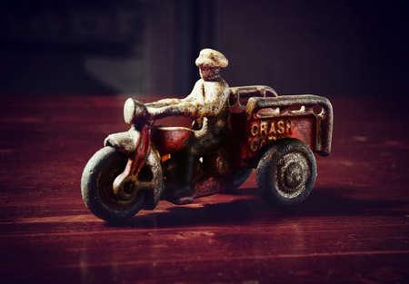 red vintage toy tricycle on dark wooden table Standard-Bild