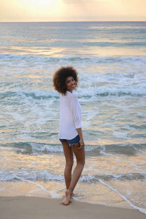 beautiful woman portrait  with afro hair relax  at sunset on the sea