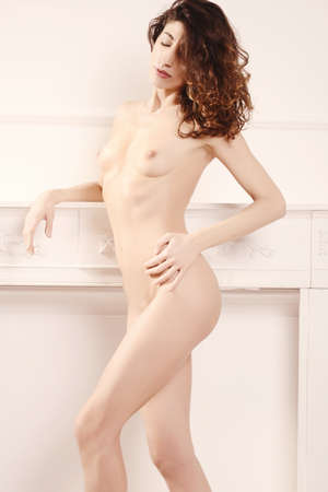 sensual woman with  sexy body in white home interior