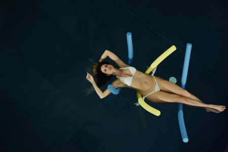 beautiful woman floating in the water in spa pool Stock Photo