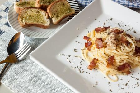 Spaghetti Carbonara and garlic bread ready serve photo