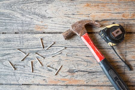 tack: Hammer , Measuring Tape and tack on wood background for repair