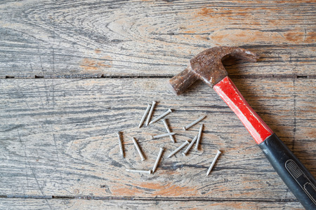 tack: Hammer and tack on wood background