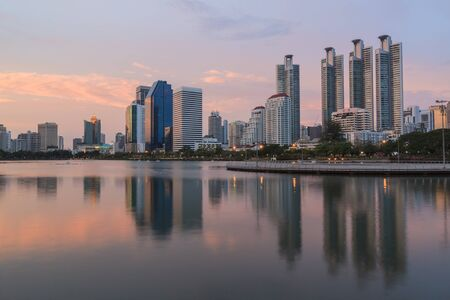 Bangkok City at twilight time and reflex of building in lake , Thailand