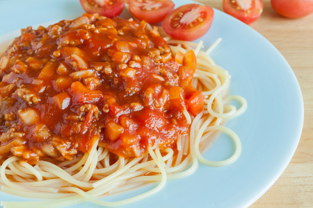 Spaghetti with tomato sauce on dish , wooden background