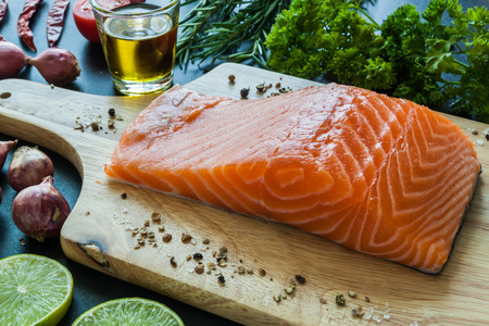 rosmarin: Salmon fillet with lemon rosemary parsley oil and garnish  on wooden board