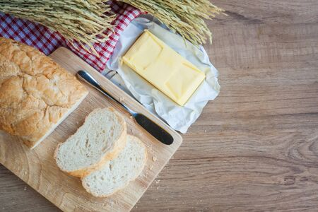 Sliced bread and butter on wood board with napery on wooden background