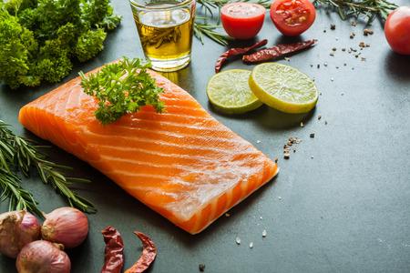 Salmon fillet with lemon rosemary parsley oil and garnish  on blackboard Zdjęcie Seryjne