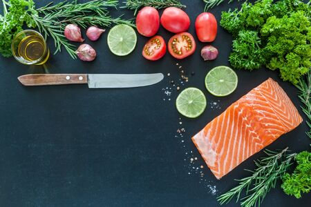 Salmon fillet with lemon rosemary parsley tomato and garnish  on blackboard ready to cook