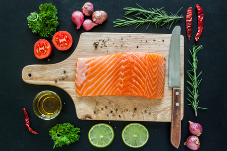 Salmon fillet on wooden board with lemon rosemary parsley and garnish  ready to cook Zdjęcie Seryjne
