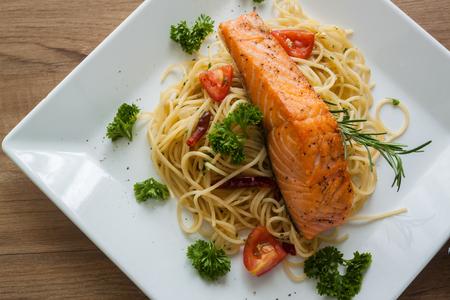 Spaghetti with salmon fillet on white dish , top view