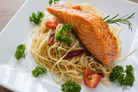Spaghetti with grilled salmon fillet on white dish