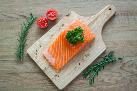 Salmon fillet on wooden board with tomato rosemary and parsley ready to cook