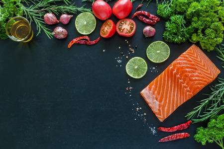 rosmarin: Salmon fillet with lemon rosemary parsley and garnish  on blackboard ready to cook Stock Photo