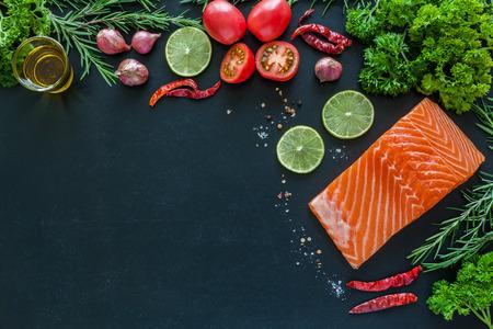 Salmon fillet with lemon rosemary parsley and garnish  on blackboard ready to cook Zdjęcie Seryjne
