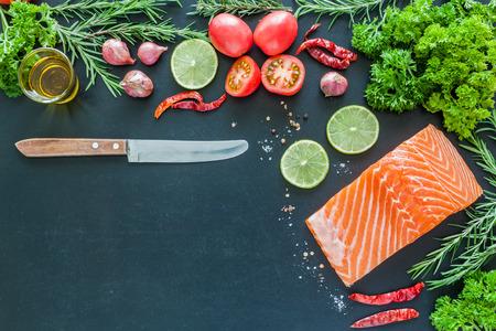 Salmon fillet with lemon rosemary parsley and garnish  on blackboard Zdjęcie Seryjne