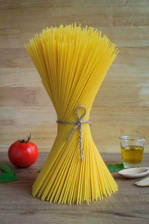 Spaghetti and tomatoes with basil and olive oil on wooden table