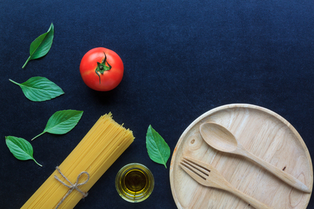 Spaghetti and tomatoes with basil and oil on blackboard