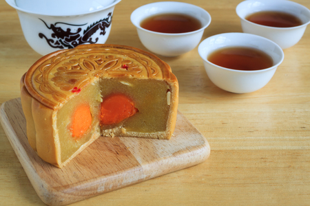 Moon Cake with tea on wooden background , dessert of Chinese mid autumn festival
